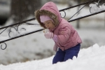 AUDREY CARSON, 3, PLAYS IN THE OCTOBER SNOW IN OMAHA / AP PHOTO