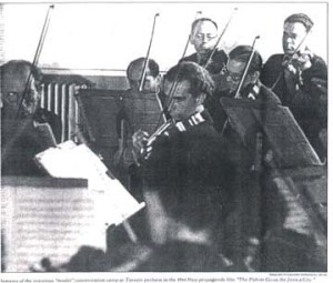An orchestra of prisoners gives one of the concerts that on the one hand were encouraged by the Nazis and on the other hand helped the victims maintain their sanity.